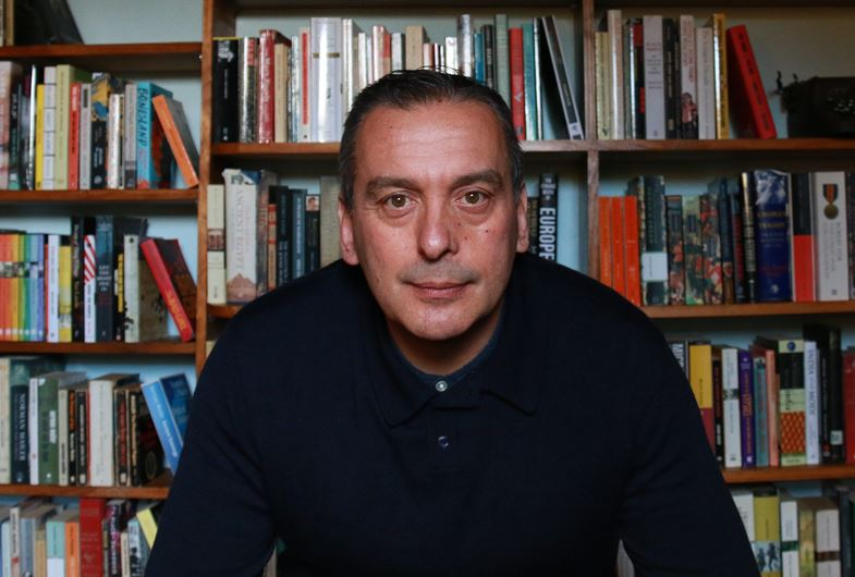 Christos Tsiolkas infront of a bookshelf.